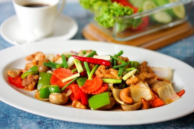 Pollo in padella con anacardi ricetta sul tavolo blu con tazza di caffè bianco e verdura