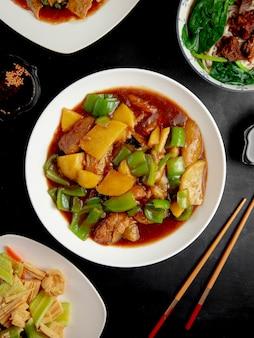 Pollo in umido con zucca e peperoni sul tavolo nero