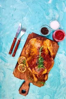 Pollo intero al forno con salse su tavola di legno su sfondo blu.