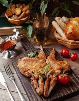 Pollo intero alla griglia con salsa di pomodoro ed erbe su tavola di legno