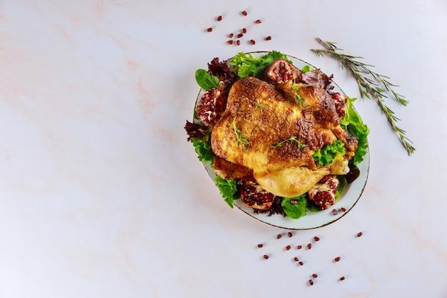 Pollo intero alla griglia sul piatto con insalata verde e melograno
