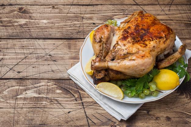 Pollo intero arrosto con limone e uva sul tavolo di legno