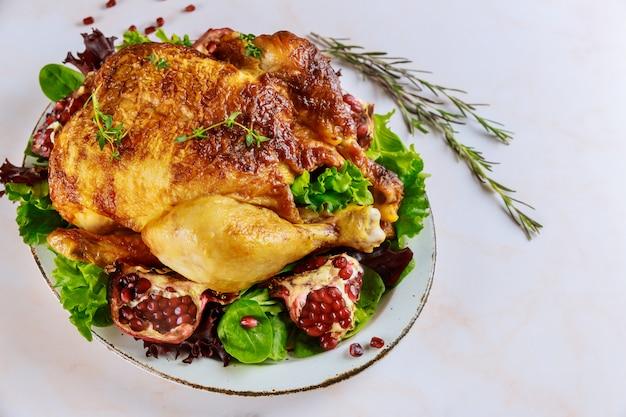 Pollo intero arrosto tradizionale sul piatto con melograno, rosmarino e insalata verde.