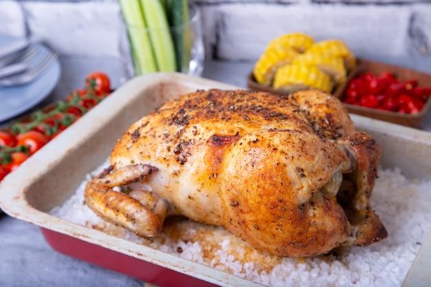 Pollo intero cotto al sale. con pannocchie, pomodorini, cetrioli e peperoni jalapeno. messa a fuoco selettiva, primo piano.