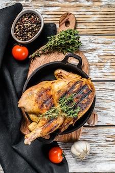 Pollo intero dell'azienda agricola al forno con timo su bianco. vista dall'alto