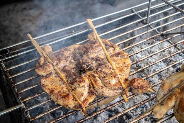 Pollo intero tailandese grigliato con carbone di legna sulla strada.
