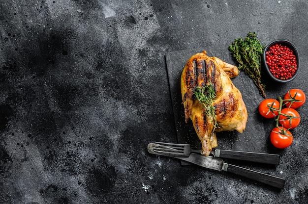 Pollo organico intero arrostito con timo sul nero. vista dall'alto. copia spazio