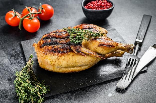 Pollo organico intero arrostito con timo sul nero. vista dall'alto
