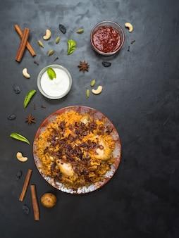 Pollo piccante delizioso biryani in ciotola bianca su fondo nero, alimento indiano o pakistano.