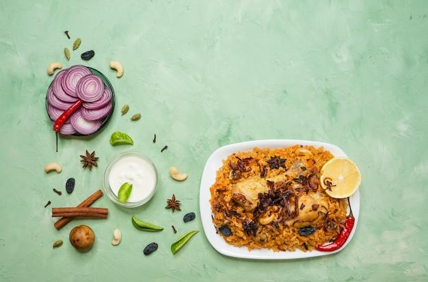 Pollo piccante delizioso biryani in ciotola bianca su fondo verde, alimento indiano o pakistano.