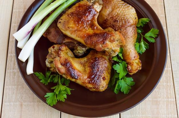 Pollo succoso arrostito (gambe, winglets) su un piatto di argilla su un tavolo di legno chiaro. la vista dall'alto