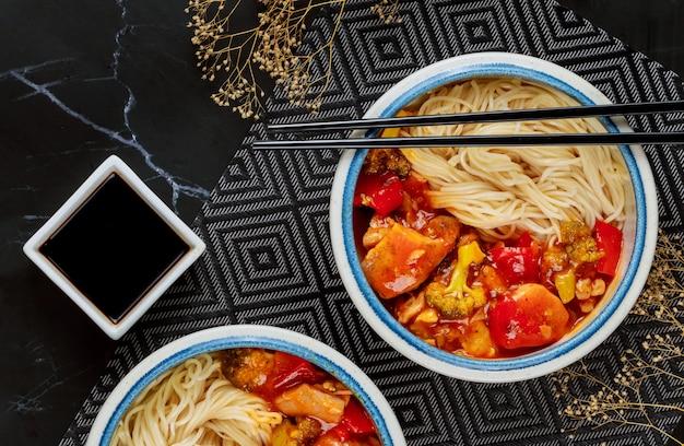 Pollo teriyaki con peperoni, broccoli e noodles in una ciotola con le bacchette.