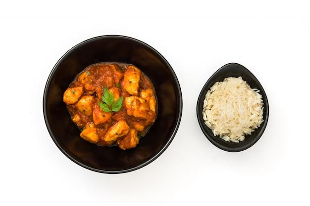 Pollo tikka masala con riso in ciotola sulla parete bianca