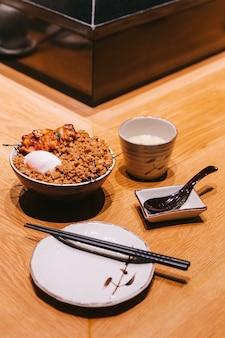 Pollo yakitori rice bowl con carne di maiale tritata servita con uovo al vapore cinese.