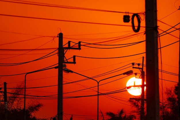 Polo elettrico e linee di trasmissione la sera. piloni di elettricità con cavo metallico e lampione al tramonto. potenza ed energia nelle città rurali. bello cielo rosso al tramonto dietro i pali elettrici.