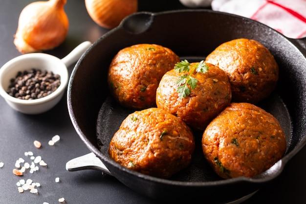 Polpetta piccante organica cruda casalinga dell'alimento in getto di ferro su fondo nero