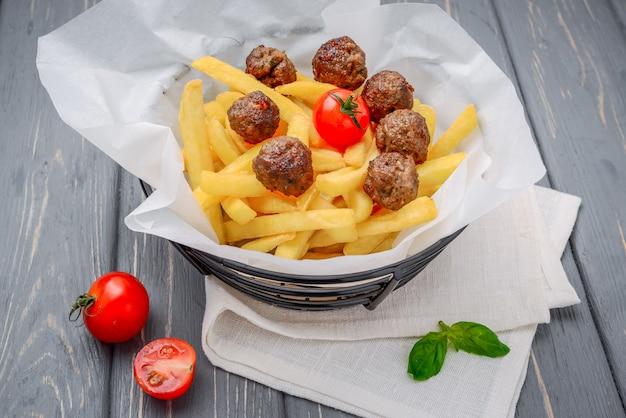 Polpette arrostite con le patate fritte sulla tavola di legno