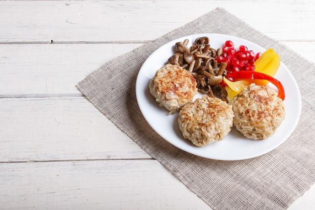 Polpette con funghi di riso, peperoni e semi di melograno su legno bianco.