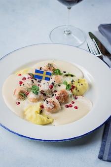 Polpette con patate bollite, salsa e frutti di bosco decorati dalla bandiera svedese