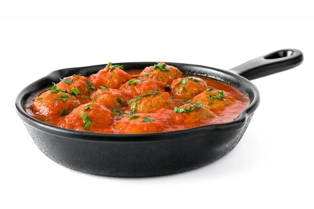 Polpette con salsa al pomodoro in padella del ferro isolata su bianco