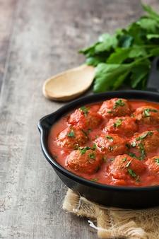 Polpette con salsa al pomodoro in padella del ferro sulla tavola di legno