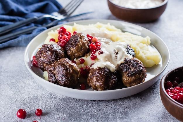 Polpette di carne di maiale e manzo fatte in casa con purè di patate su una tabella di sfondo concreto di pietra grigia