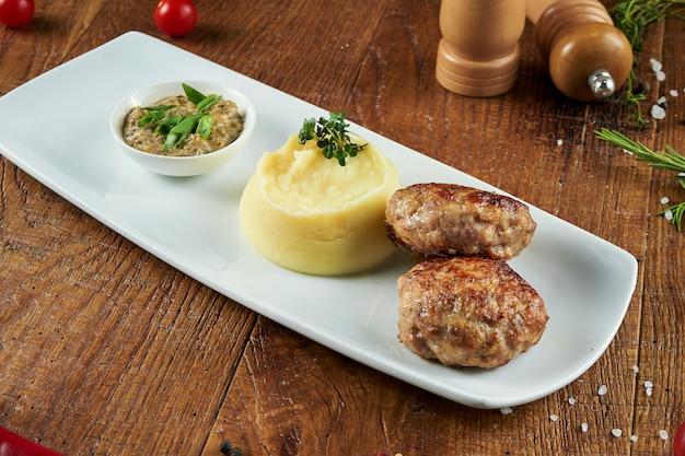 Polpette di coniglio fritto (cotolette) guarnite con piselli, purè di patate e cetriolo in un piatto bianco su una superficie di legno