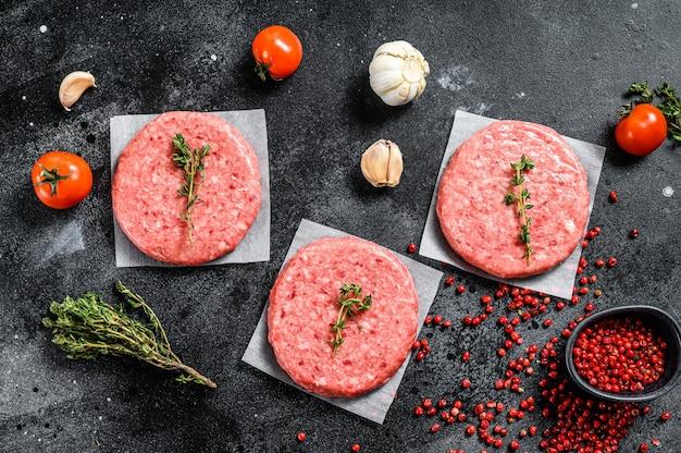 Polpette di hamburger, terra fresca cruda, tritare la carne sul nero. vista dall'alto