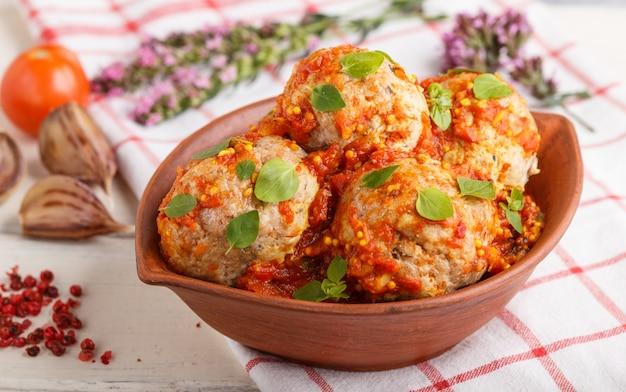 Polpette di maiale con salsa di pomodoro, foglie di origano, spezie ed erbe aromatiche in ciotola di argilla con tessuto di lino. vista laterale