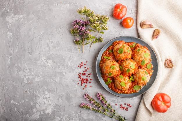 Polpette di maiale con salsa di pomodoro, foglie di origano, spezie ed erbe aromatiche. vista dall'alto
