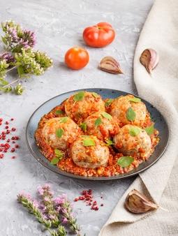 Polpette di maiale con salsa di pomodoro, foglie di origano, spezie ed erbe aromatiche. vista laterale