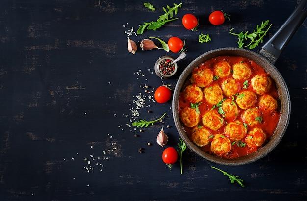 Polpette di pollo con salsa di pomodoro in padella. cena. vista dall'alto. sfondo scuro