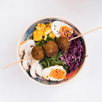 Polpette di pollo fritto sul bastone sopra la ciotola con funghi; mais; uovo; insalata di cavoli e alghe