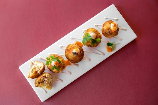 Polpette di pollo ripiene guarnite con panna e salsa