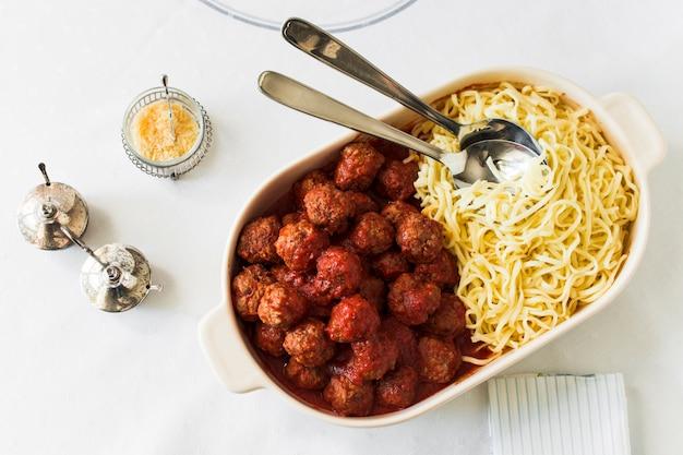 Polpette e trenette nella scatola bianca del pranzo con i cucchiai