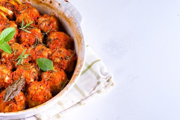 Polpette fatte in casa con salsa di pomodoro in un piatto bianco al forno con erbe