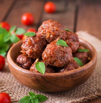 Polpette in salsa al pomodoro agrodolce e basilico in una ciotola di legno