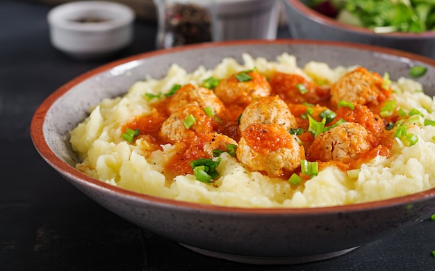 Polpette in salsa di pomodoro con purè di patate in ciotola.