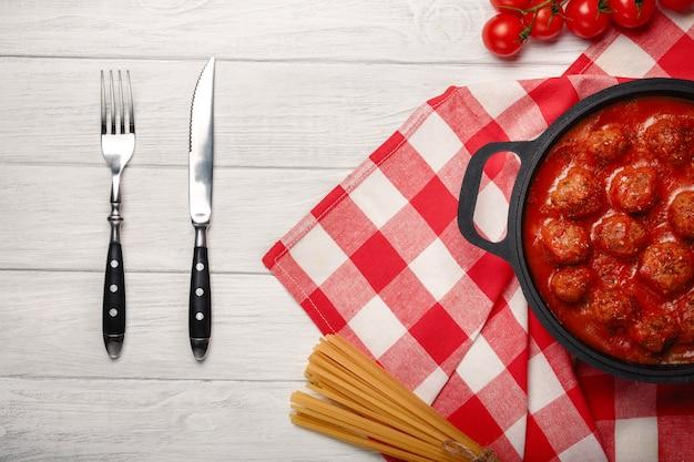 Polpette in salsa di pomodoro con spezie in una padella su una tavola di legno bianca