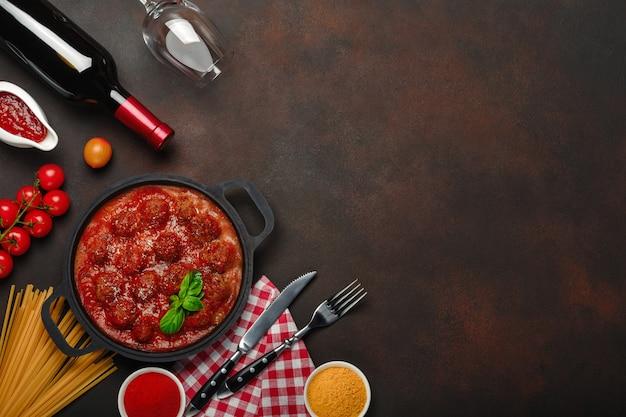 Polpette in salsa di pomodoro con spezie, pomodorini, pasta e basilico in una padella con una bottiglia di vino