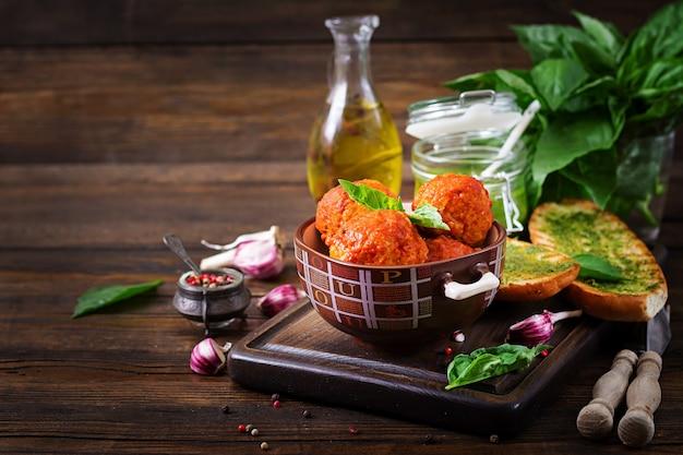 Polpette in salsa di pomodoro e pane tostato con pesto di basilico. cena. cibo gustoso.