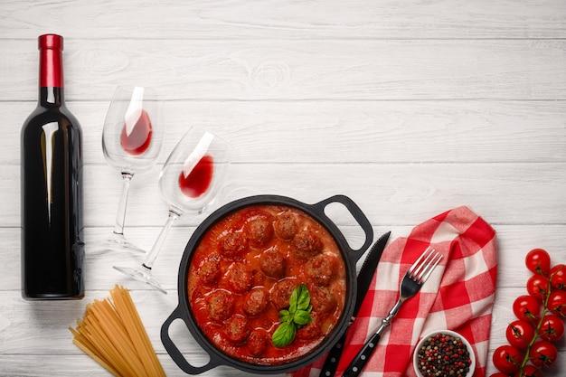 Polpette in salsa di pomodoro in una padella con ciliegia, pomodori, bottiglia di vino e due bicchieri su una tavola di legno bianca