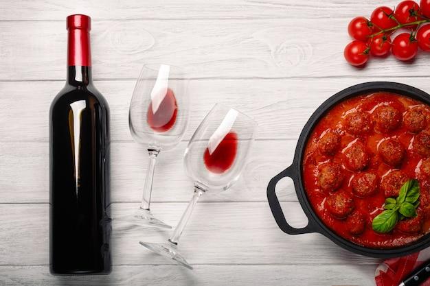 Polpette in salsa di pomodoro in una padella con ciliegia, pomodori, bottiglia di vino e due bicchieri