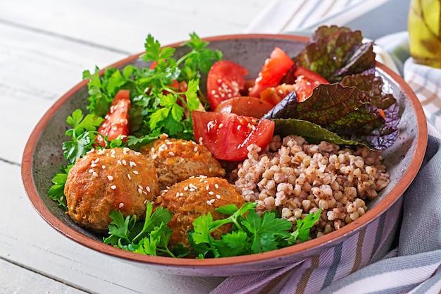 Polpette, insalata di pomodori e porridge di grano saraceno sulla tavola di legno bianca. cibo salutare. pasto dietetico. ciotola di buddha.