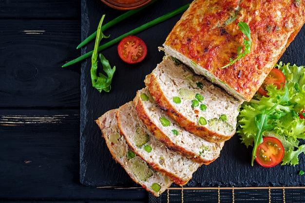 Polpettone al forno di pollo al forno fatto in casa saporito con i piselli ed i broccoli sulla tavola nera.