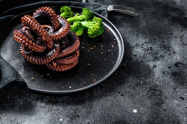 Polpo intero alla griglia con broccoli su un piatto. vista dall'alto. copia spazio