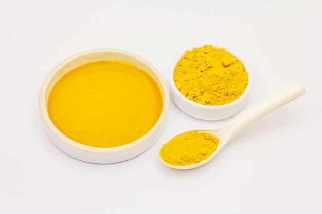 Polvere asciutta e miele della curcuma isolati su fondo bianco