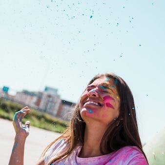 Polvere blu di holi sopra la giovane donna sorridente all'aperto