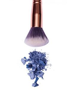 Polvere blu e grigia dell'ombretto con la spazzola, isolata