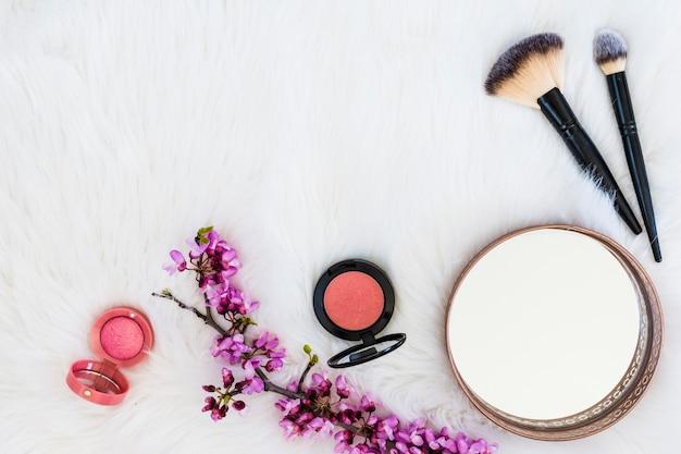 Polvere compatta rosa con rametto di fiori; pennelli specchio e trucco su sfondo di pelliccia bianca